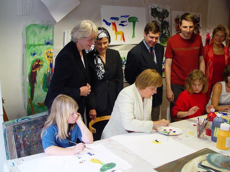 2004 malt Angela Merkel mit Kindern in der Malschule der Kunsthalle