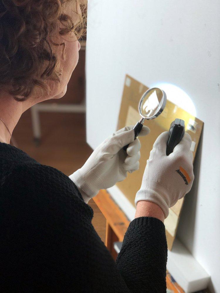 Katharina Rüppell untersucht mit der Lupe die Werkrückseiten