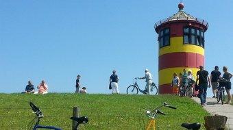 Mit dem Rad am Pilsumer Leuchtturm. Er wurde durch Otto Waalkes berühmt.