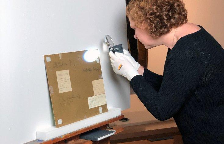 Katharina Rüppell untersucht eine Bildrückseite